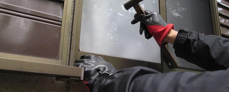 窓ガラスを割って侵入を試みる窃盗犯